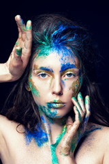 Beautiful face with colored paint on a black background. Beautiful girl. Colorful makeup. Fashionable woman. Toned image.