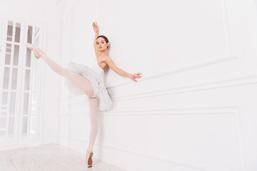 Graceful classical dancer stretching her left leg
