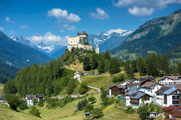 Tarasp Castle surrounded by larch and pine forest in the Lower Engadine Valley, Switzerland, Europe