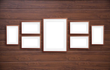 Blank frames collage on brown wooden panels wall
