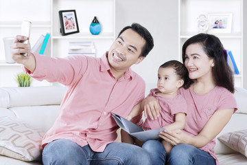Happy family taking selfie picture on sofa