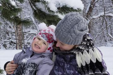 Мама в зимнем лесу обнимает ребенка. Девочка смеется.