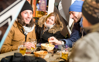 Happy friends drinking beer and eating chips - Cheerful people having fun at bar restaurant by skiing resort with snow equipment - Friendship concept on warm night filter with focus on young woman