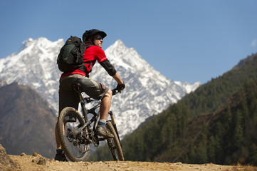 A mountain biker in the Tsum Valley looks at Ganesh Himal mountains, Manaslu region, Himalayas, Nepal, Asia