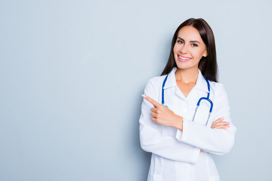 Smiling happy doctor pointing with finger on blue background