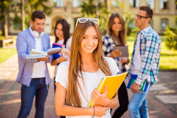 happy cute girl standing near university and holding notebook