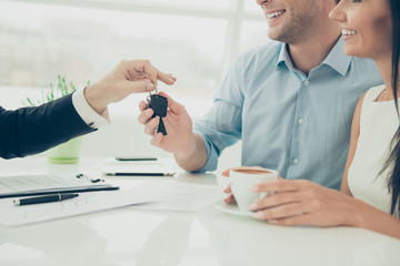 Close up photo of broker giving keys of new house to happy coupl