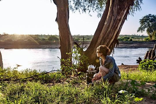 A young woman observes the early morning light while camping in Samburu National Park, Kenya