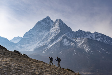 Hikers walking in Himalayas with Ama Dablam in distance, Nepal