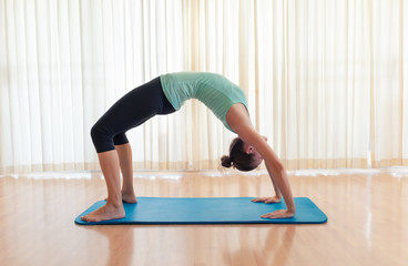 Female doing flexible yoga pose.