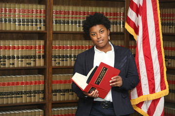 Portrait of an attractive African American female lawyer, in law library