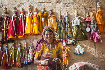 A woman sells puppets along the fort walls in Jaisalmer in the desert state of Rajasthan, India, Asia