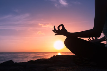 Hand of a woman meditating in a yoga pose on the beach.    Wall mural
