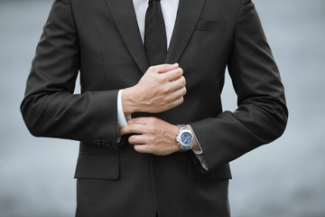 Closeup of man wearing suit and watch.