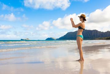 Female tourist walking on the beach taking photos. Location Hawaii.