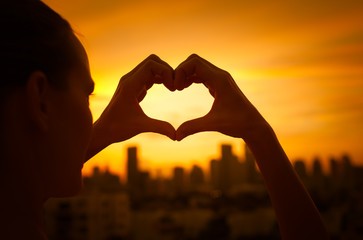 Silhouette of girl holding up heart against a beautiful sunset. Giving and love in the city concept.