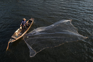 Asian fisherman on wooden boat casting a net for catching freshwater fish in nature river in the early morning.