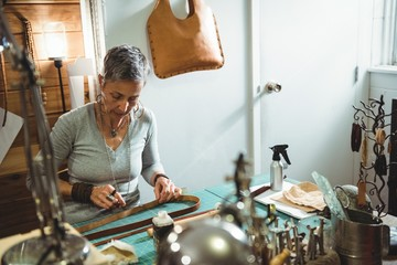 Attentive craftswoman cutting leather