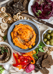 Vegetarian snack table. Pumpkin, beets hummus, beans and mushroom pate, vegetables, nuts, bread on a wooden table, top view. Flat lay
