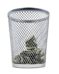 Wasting money. Isolated dollar bills inside of a trash bin.