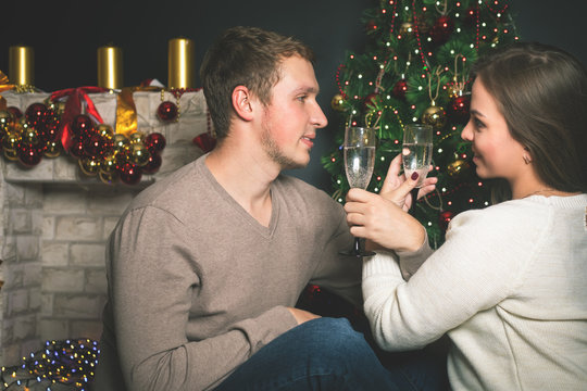 Couple young near decorated Christmas tree celebrating New Year