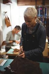 Attentive craftswoman cutting leather