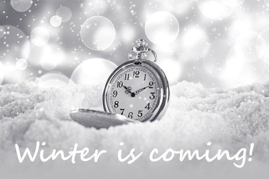 Pocket watch and text WINTER IS COMING on snow background