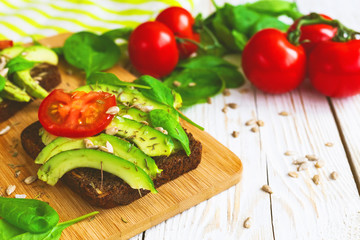 Toast with sliced avocado, tomatoes, spinach and spices