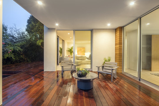 Wooden deck / balcony at night with furniture and open doors lea