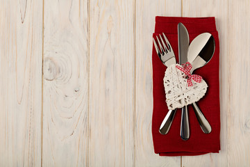 Valentine's day concept. On the wooden table cutlery on linen na