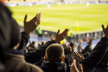 Silhouettes and hands of fans at a football stadium