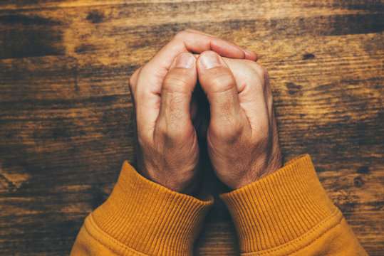 Top view of religious male crossed hands in prayer