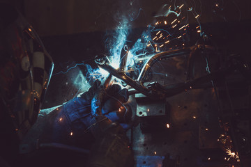 Man welding steel pipe on a work table in an Industrial workshop, producing blue and green smoke, hot sparks