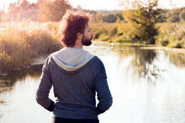Back of man looking at river, free space. Young stylish guy enjoying beautiful nature landscape at sunrise. Relax, nature, calm, pacification concept