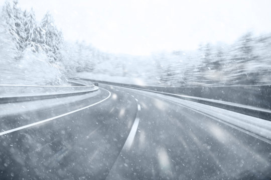 Dangerous winter season car driving on slippery highway. Heavy snowfall conditions on the highway.