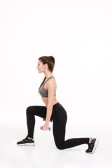 Portrait of a young pretty sportswoman doing squats with dumbbells