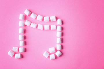 Musical note made of marshmallow on pink background