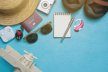 Accessories for travel. Passport, Earphone, sunglasses, Headlamps, hat, camera and a plane. Top view. Holidays and tourism concept..