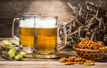 Photo of couple beers with pretzels, wheat spikes, hops