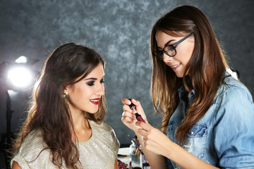 Professional makeup artist working with beautiful young woman