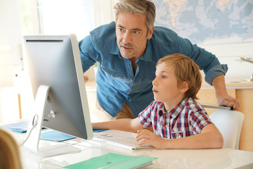 Schoolboy in computer lab with teacher helping