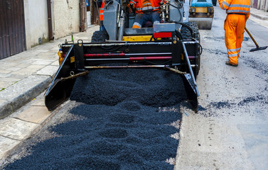 lightl truck laying fresh bitumen and asphalt at road construction site