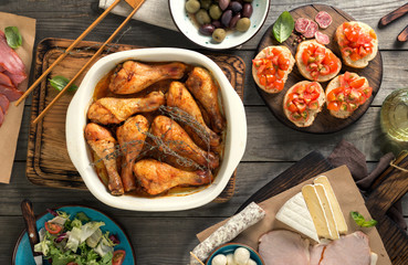 Baked chicken legs with variety of snacks on wooden table