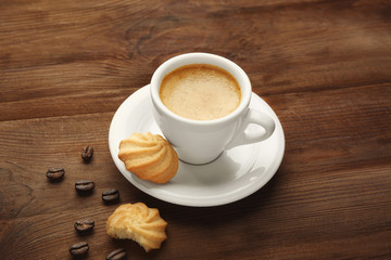 Cup of tasty coffee with cookies and beans on wooden table