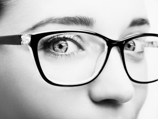 Beautiful young woman wearing glasses close-up isolated on white