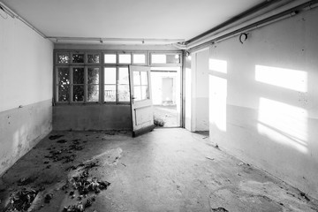 House that no longer exists. Old abandoned house. The room is destroyed, the walls are broken, trash on the floor, chaos. Selective focus. Black and White.