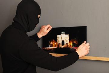 Maskierter Mann beim Bilder klauen
