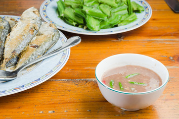 a cup of shrimp paste serving with fried mackerel and vegetable on wood table
