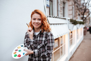 Cheerful young lady painter with red hair walking on street
