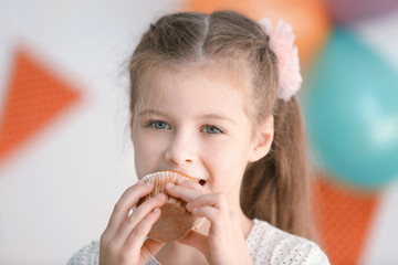 Cute little girl eating tasty muffin, close up view
